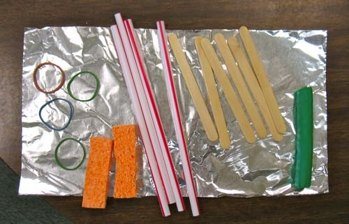 4 rubber bands, 4 straws, 6 popsicle sticks, a stick of clay, and a 6x12 inch shhet of alumimum foil